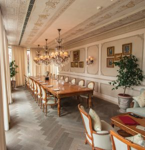 Beige color dining room with wooden chairs and table, many frames mounted on the wall and lantern hung in the ceiling