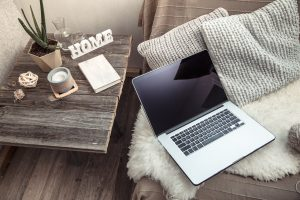 rustic room with a laptop, and a deside table with notebook, and rustic decorative items