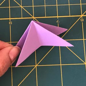 a hand holding origami paper with purple color forming 4 triangles