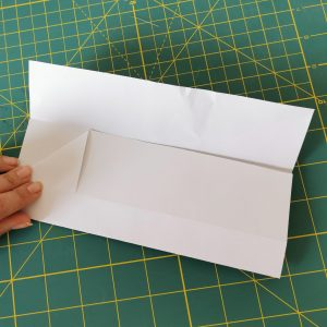 Hand making a triangle on a wite origami paper over a green mat