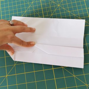 Hand holding origami paper with white A4 over a green mat