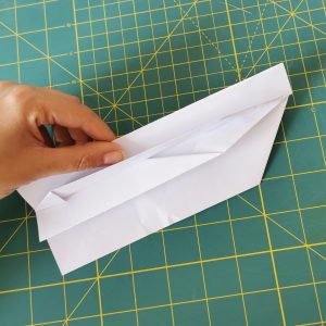 a hand holding a folded white origami paper over a green mat