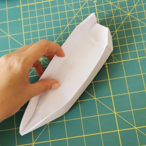 a hand holding a canoe white origami over a green mat