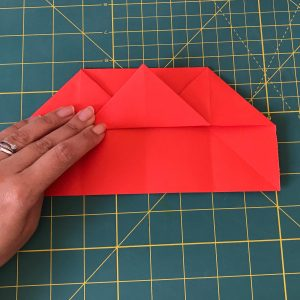 Hand holding red origami paper in the form of a house over a green mat