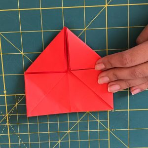 Hand holding origami red paper in the form of squares and triangles over a green mat