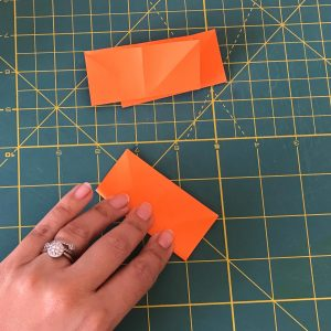 A hand folding an orange postlet in rectangle shape over a green matt with 2 other postlets in the background