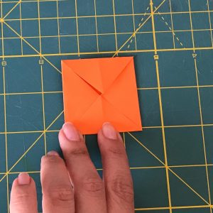 Hand folding a post-let over a green mat in square shape by making 4 triangles