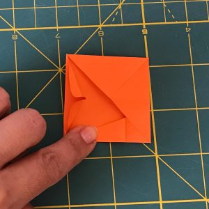 Hand holding small triangles made with a post-let to create elevated tops over a green mat