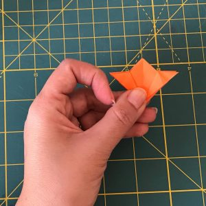 Flattened orange post let after doing origami DIY in the shape of a flower and held with a hand over a green mat