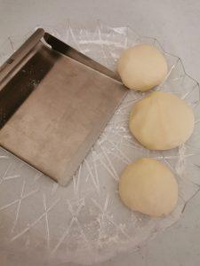 Dough balls left to rest next to a dough slicer