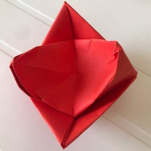Red crown with origami paper over a white table