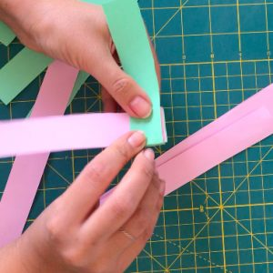 hand folding green and pink paper strips on each others over a green mat