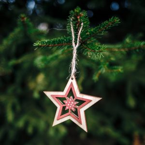 A vertical shot of a wooden star-shaped Christmas ornament hanging from a pine tree