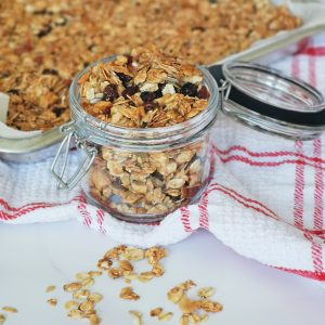 a jar of granola with a granola tray behind
