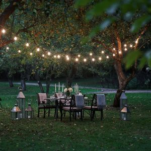 string lights over a seating space in a garden